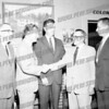 Looks like a 1958 Nelson Rockefeller shaking hands left while Assemblyman Don Campbell, center, looks on. Painting on wall looks like Old Fort Johnson.