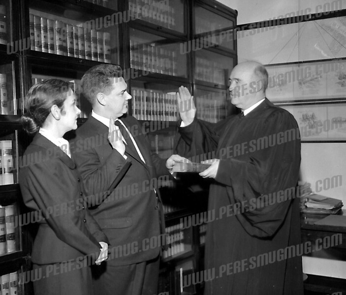 Police Court Judge Malcolm Tomlinson being administered the oath of office by Judge Chandler Knight. 1950's.