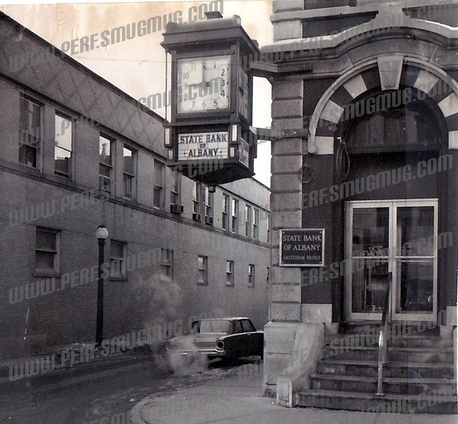 "49 East Main Street, corner of Railroad Street. The landmark clock disappeared for several years when it was appropriated for the main office of the State Bank of Albany and then returned to Amsterdam about 1966. When the new branch office was built across the street (now the ""For Sale"" Bank of America) the clock didn't fit into the decor and so left Amsterdam again"