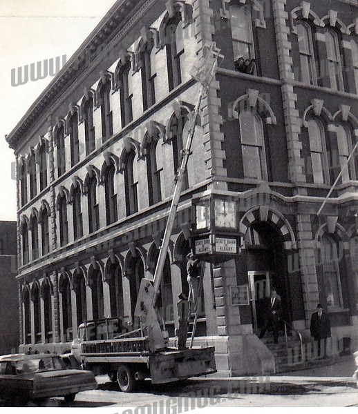"""49 East Main Street, corner of Railroad Street. The landmark clock disappeared for several years when it was appropriated for the main office of the State Bank of Albany and then returned to Amsterdam about 1966. When the new branch office was built across the street (now the """"For Sale"""" Bank of America) the clock didn't fit into the decor and so left Amsterdam again."""