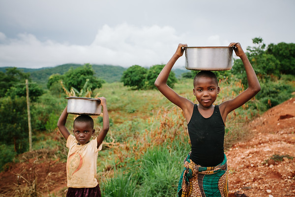 Two young girls make a trip for fresh water.  It is very common for young kids, girls especially, to stop going to school in order to help with common survival tasks like getting water.