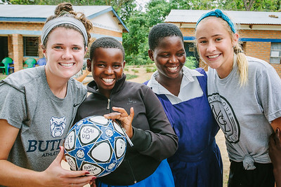 Girls receive a ball from college soccer players.  With hope, these girls too will be able to go to college with a scholarship to play soccer.  A rare opportunity for many girls.