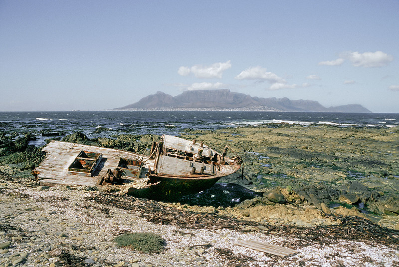 "Wrecked fishing boat on Robben Island, Cape Town in background, South Africa<br /> <br /> Taken from my archives and posted today in memory of Nelson Mandela, the remarkable South African who died yesterday at the age of 95.<br /> <br /> I first visited South Africa in 1984 when it was still  under the apartheid regime, and Nelson Mandela was imprisoned on Robben Island off the south coast of Cape Town.  I visited again in 2000 after the Truth and Reconciliation hearings and made a trip to Robben Island to see the prison there and the cell where Mandela had been imprisoned for much of his 27 years in prison.  I took this picture on the beach of Robben Island and I like to think that Madiba may have stood on this very spot by the old wrecked boat and enjoyed this view of Cape Town.<br /> <br /> In the winter of 1964, Nelson Mandela arrived on Robben Island where he would spend 18 of his 27 prison years. Confined to a small cell, the floor his bed, a bucket for a toilet, he was forced to do hard labor in a quarry. He was allowed one visitor every 6 months for 30 minutes. He could write and receive one letter of 500 words every six months. But Robben Island became the crucible which transformed him. Through his intelligence, charm and dignified defiance, Mandela eventually bent even the most brutal prison officials to his will, assumed leadership over his jailed comrades and became the master of his own prison. He emerged from it the mature leader who would fight and win the great political battles that would create a new democratic South Africa.  Mandela was released from Robben Island in 1990 and four years later the prisoner became the President. Adapted from <a href=""http://www.pbs.org/wgbh/pages/frontline/shows/mandela/prison/"">http://www.pbs.org/wgbh/pages/frontline/shows/mandela/prison/</a><br /> <br /> A panorama of Cape Town taken from the boat to Robben Island can be seen here: <a href=""http://goo.gl/KLboKD"">http://goo.gl/KLboKD</a><br /> <br /> 06/11/13  <a href=""http://www.allenfotowild.com"">http://www.allenfotowild.com</a>"
