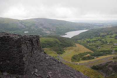 "A view over the landscaped Allt Ddu Quarry, Llyn Padarn, and Angelsey. The original rail access to the quarry was at this level and the paths trace the lisnes of tramways.   The ""village tramway"" ran from here to the Mills level and is now a public path through the middle of te quarry"
