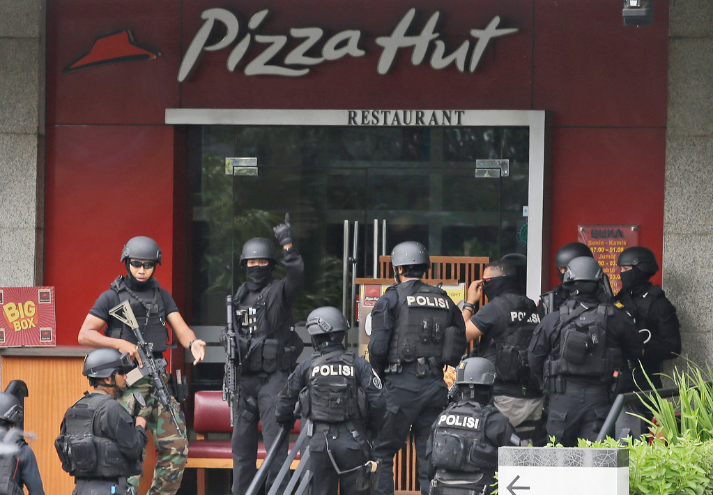 . Police officers gather outside a Pizza Hut restaurant next door to a Starbucks cafe which was attacked in Jakarta, Indonesia Thursday, Jan. 14, 2016. Attackers set off explosions at a Starbucks cafe in a bustling shopping area in Indonesia\'s capital and waged gunbattles with police Thursday, leaving bodies in the streets as office workers watched in terror from high-rise windows. (AP Photo/Achmad Ibrahim)