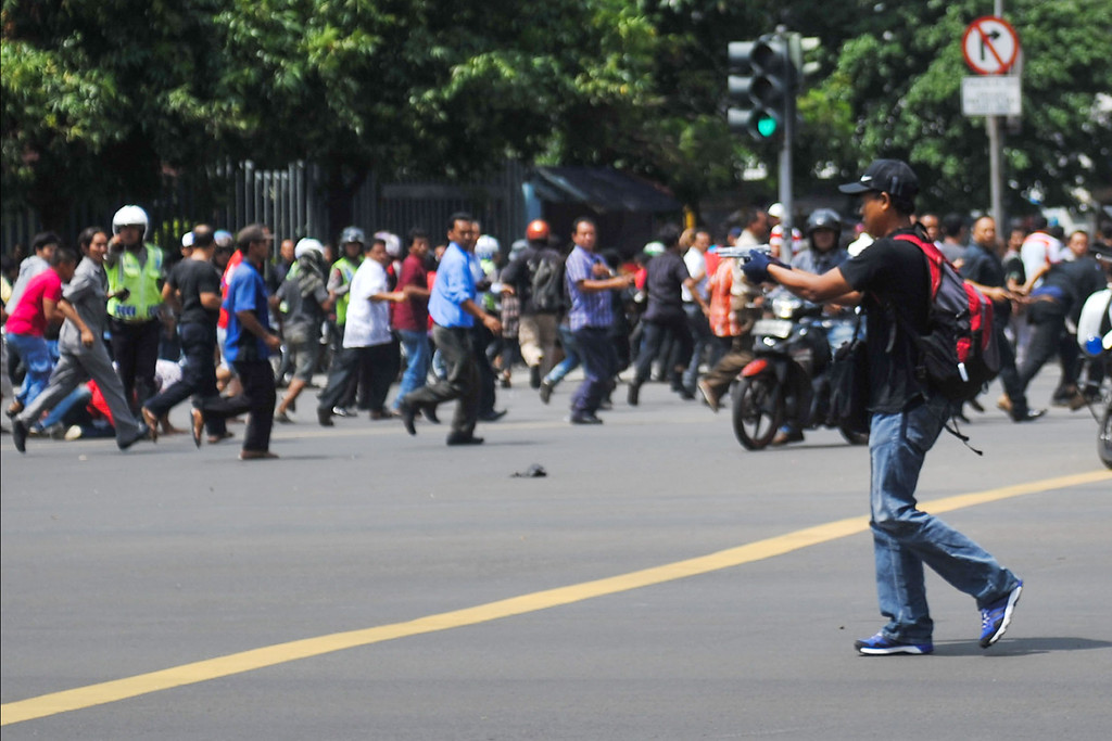 . In this photo released by China\'s Xinhua News Agency, an unidentified man with a gun walks in the street as people run in the background on Thamrin street near Sarinah shopping mall in Jakarta, Indonesia, Thursday, Jan. 14, 2016. Suicide bombers exploded themselves in downtown Jakarta on Thursday while gunmen attacked a police post nearby, a witness told The Associated Press. Local television reported more explosions in other parts of the city. (Veri Sanovri/Xinhua via AP) NO SALES