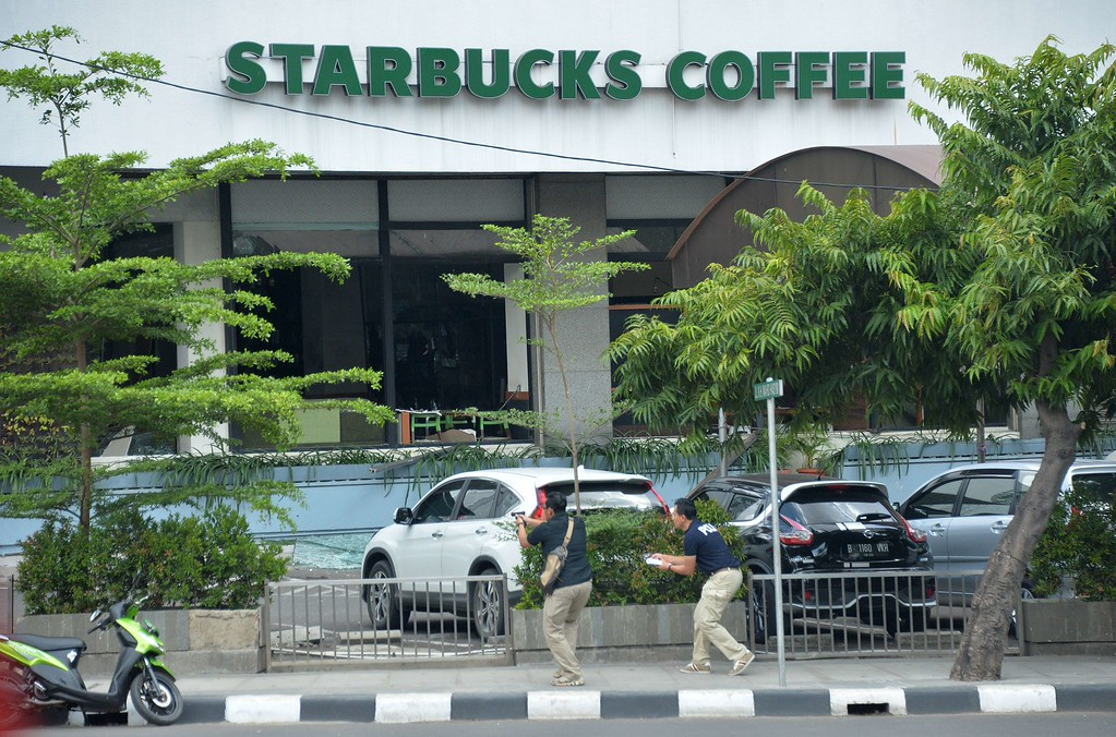 . Plainclothes police aim their handguns towards suspects outside a cafe after a series of blasts hit the Indonesia capital Jakarta on January 14, 2016. A series of bombs killed at least three people in the Indonesian capital Jakarta on January 14, with shots fired outside a cafe as police moved in, an AFP journalist at the scene said.     AFP PHOTO / Bay ISMOYOBAY ISMOYO/AFP/Getty Images