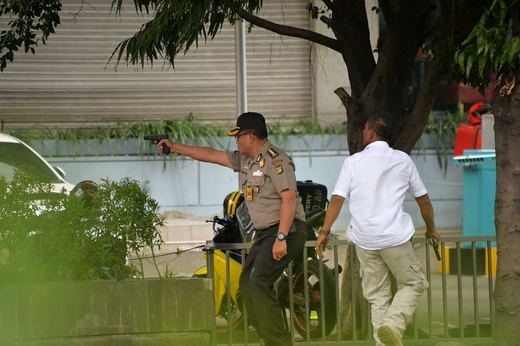 . An Indonesian policeman fires his handgun towards suspects outside a cafe after a series of blasts hit the Indonesia capital Jakarta on January 14, 2016. A series of bombs killed at least three people in the Indonesian capital Jakarta on January 14, with shots fired outside a cafe as police moved in, an AFP journalist at the scene said.     AFP PHOTO / Bay ISMOYOBAY ISMOYO/AFP/Getty Images