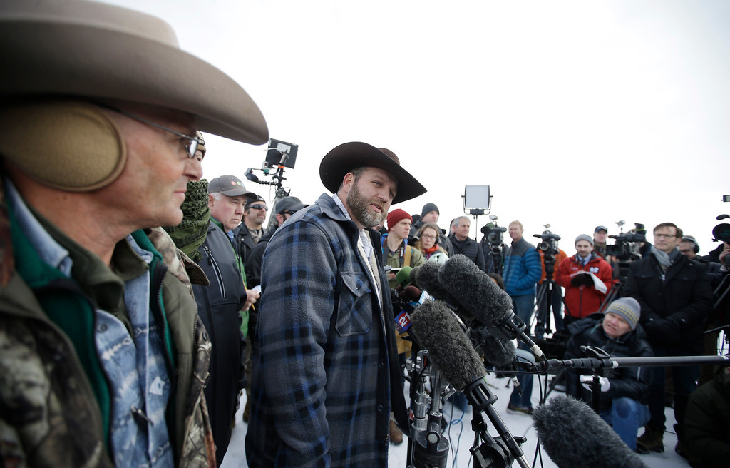 . Ammon Bundy, center, one of the sons of Nevada rancher Cliven Bundy, speaks with reporters during a news conference at Malheur National Wildlife Refuge headquarters Monday, Jan. 4, 2016, near Burns, Ore. Bundy, who was involved in a 2014 standoff with the government over grazing rights, told reporters on Monday that two local ranchers who face long prison sentences for setting fire to land have been treated unfairly. (AP Photo/Rick Bowmer)