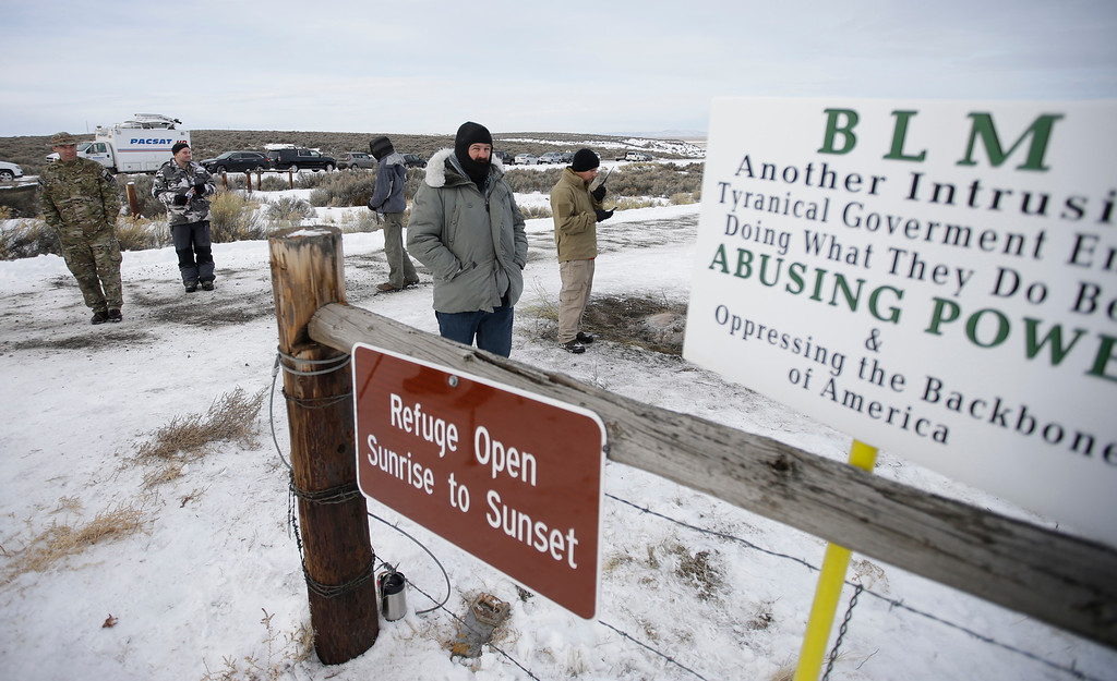 ". Members of the group occupying the Malheur National Wildlife Refuge headquarters stand guard Monday, Jan. 4, 2016, near Burns, Ore. The group calls itself Citizens for Constitutional Freedom and has sent a ""demand for redress\"" to local, state and federal officials. Ammon Bundy told reporters on Monday that two local ranchers who face long prison sentences for setting fire to land have been treated unfairly. (AP Photo/Rick Bowmer)"