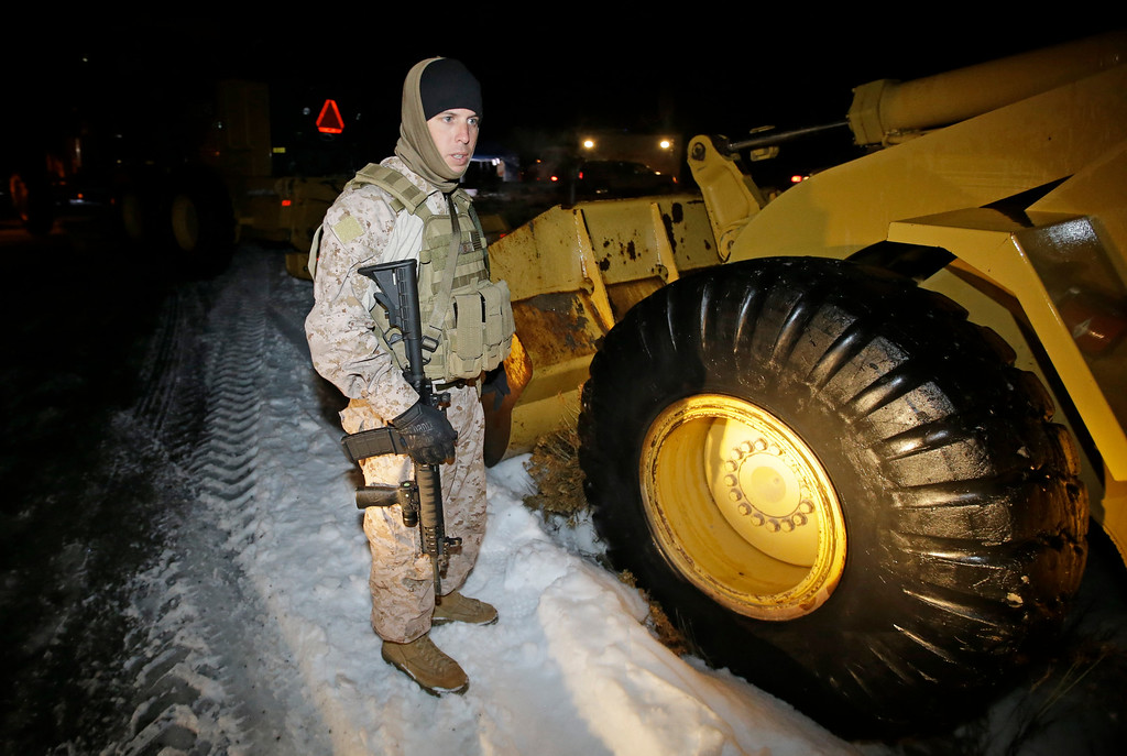 . A member of the group occupying the Malheur National Wildlife Refuge headquarters stands guard Tuesday, Jan. 5, 2016, near Burns, Ore. Ammon Bundy, the leader of a small, armed group that is occupying a remote national wildlife preserve in Oregon said Tuesday that they will go home when a plan is in place to turn over management of federal lands to locals. (AP photo/Rick Bowmer)