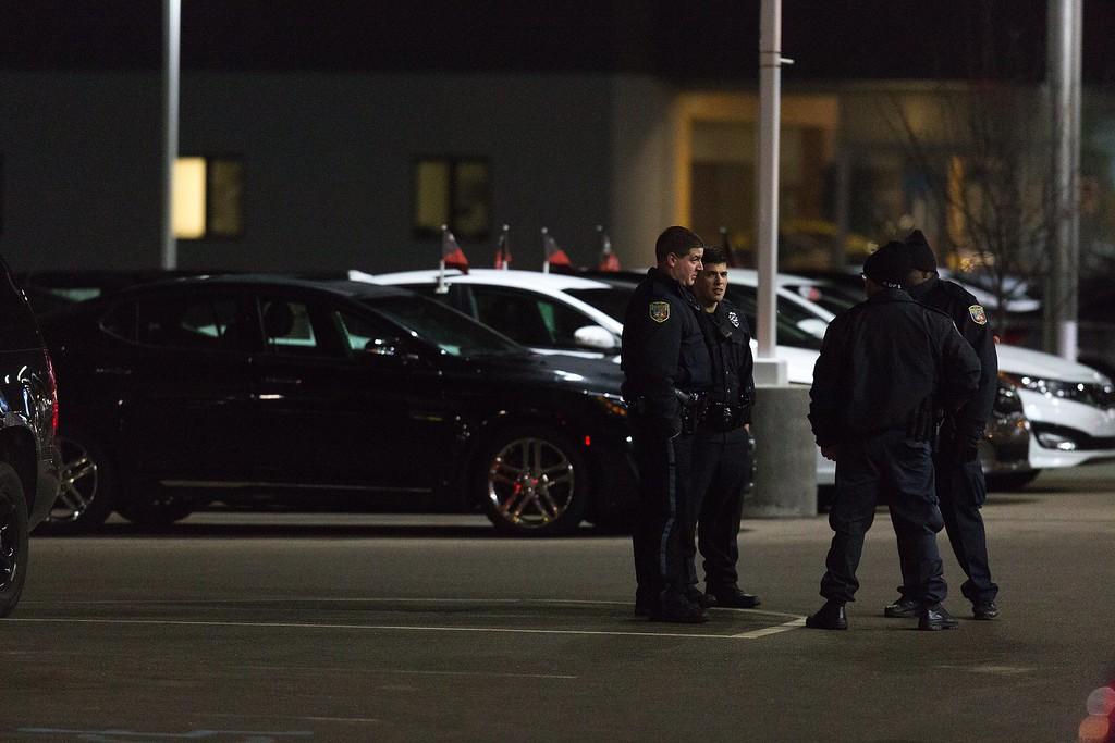 . Police the area in the parking lot of a car dealership, after a random shooting on Sunday, Feb. 21, 2016 in Kalamazoo. Jason Dalton of Kalamazoo County was arrested early Sunday in downtown Kalamazoo following a massive manhunt after several victims were shot at random.  (Bryan Bennett/Kalamazoo Gazette-MLive Media Group via AP) LOCAL TELEVISION OUT; LOCAL RADIO OUT; MANDATORY CREDIT
