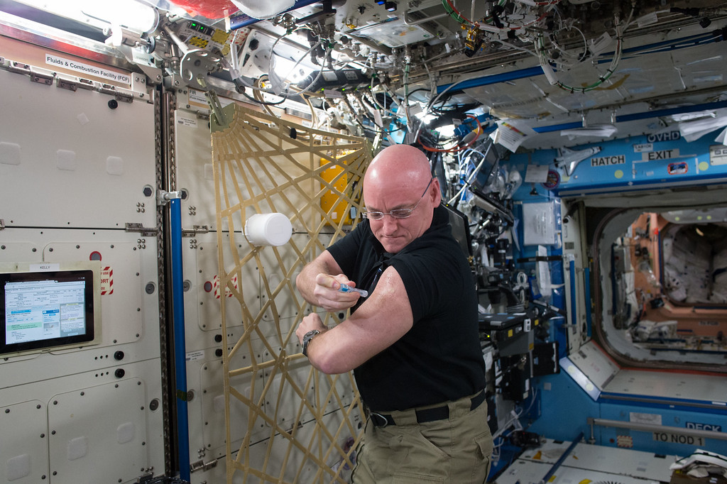 . In this Sept. 24, 2015 photo made available by NASA, astronaut Scott Kelly gives himself a flu shot aboard the International Space Station for an ongoing study on the human immune system. The vaccination is part of NASA\'s Twins Study, a compilation of multiple investigations that take advantage of a unique opportunity to study identical twin astronauts Scott and Mark Kelly, while Scott spends a year aboard the station and Mark remains on Earth. (NASA via AP)