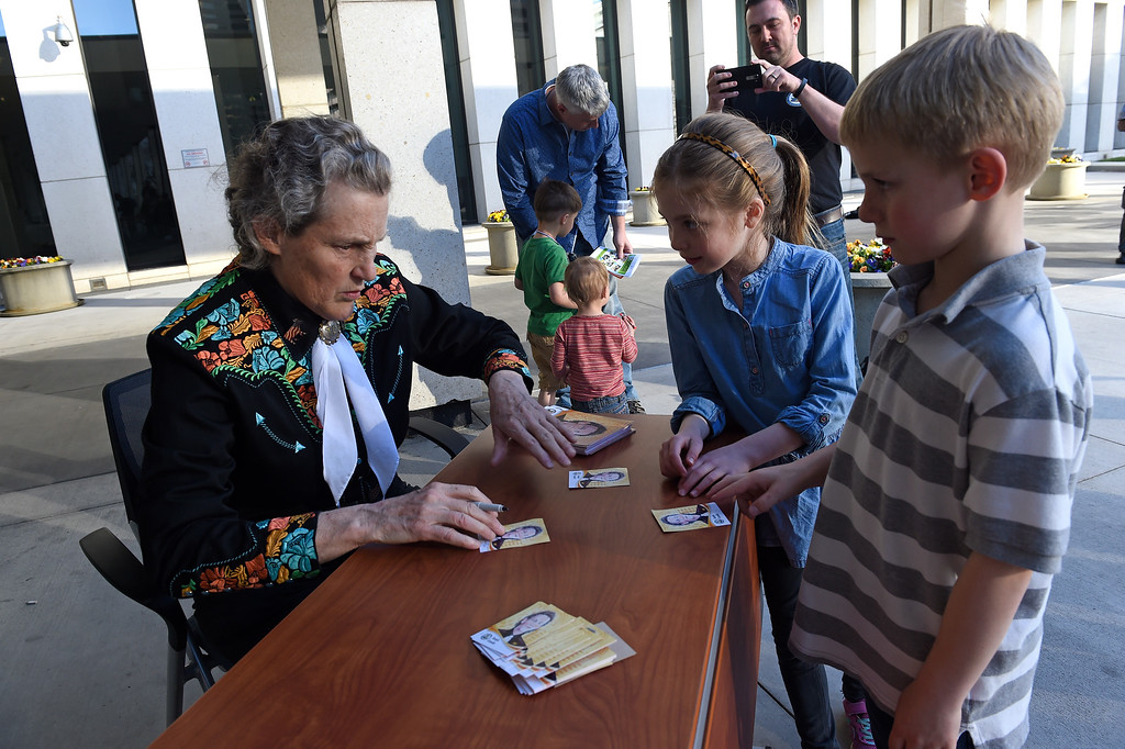 . DENVER, CO - MARCH 3: Dr. Temple Grandin, left, autographs her inventor\'s trading card for Liam McAlpine, 7, right and Julia Todd, 7, middle, outside of the US Patent and Trademark Office on April 3, 2016 in Denver, Colorado. Grandin, who is a professor of animal science at Colorado State University, is the first woman to be honored by the USPTO on it\'s kid friendly inventor trading cards.  Grandin, who is autistic, is well known for her innovative equipment designs that have greatly improved conditions for animals in the livestock industry. (Photo by Helen H. Richardson/The Denver Post)