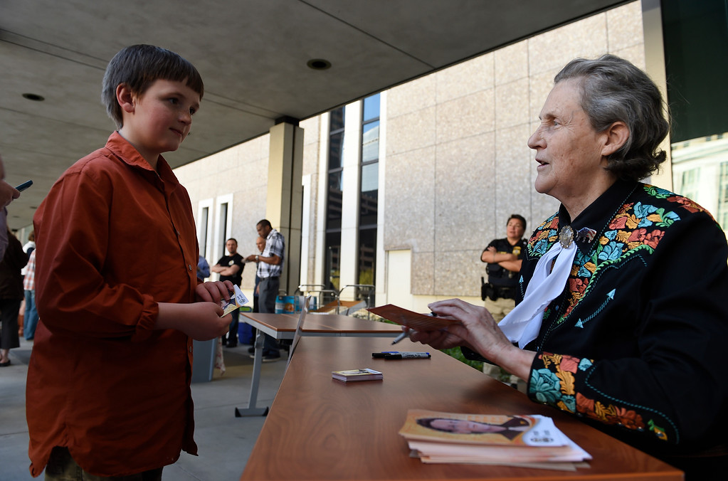 . DENVER, CO - MARCH 3: Dr. Temple Grandin talks with fan Edward Jeffers, 10, of Evergreen, after autographing one of her  inventor\'s trading card for him outside of the US Patent and Trademark Office on April 3, 2016 in Denver, Colorado. Grandin, who is a professor of animal science at Colorado State University, is the first woman to be honored by the USPTO on it\'s kid friendly inventor trading cards.  Grandin, who is autistic, is well known for her innovative equipment designs that have greatly improved conditions for animals in the livestock industry. (Photo by Helen H. Richardson/The Denver Post)