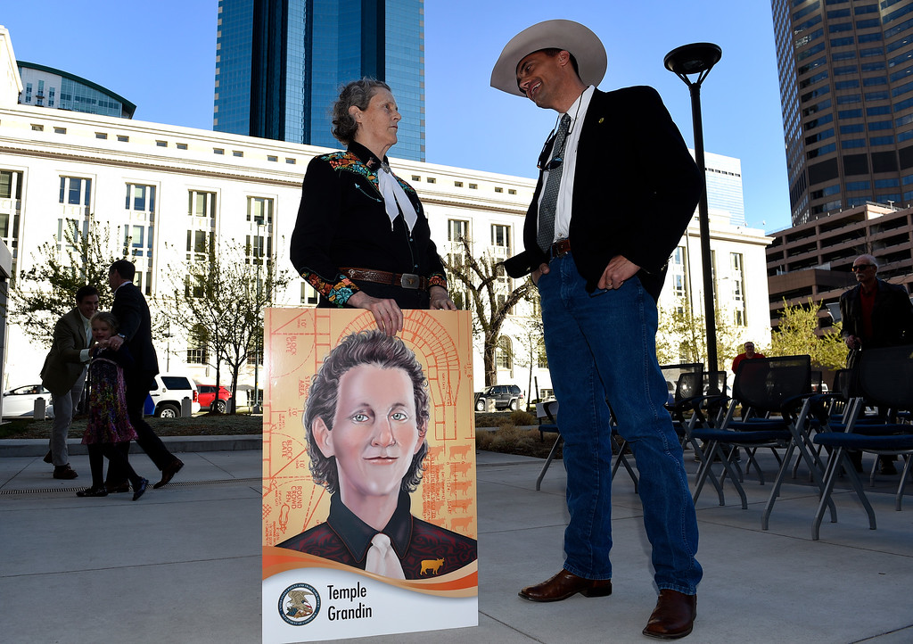 . DENVER, CO - MARCH 3: Dr. Temple Grandin holds a poster sized image of her trading card as she speaks with Todd Ingle, vice president of the Colorado Cattlemen\'s Association, after speaking  outside of the US Patent and Trademark Office on April 3, 2016 in Denver, Colorado. Grandin, who is a professor of animal science at Colorado State University, is the first woman to be honored by the USPTO on it\'s kid friendly inventor trading cards.  Grandin, who is autistic, is well known for her innovative equipment designs that have greatly improved conditions for animals in the livestock industry. (Photo by Helen H. Richardson/The Denver Post)