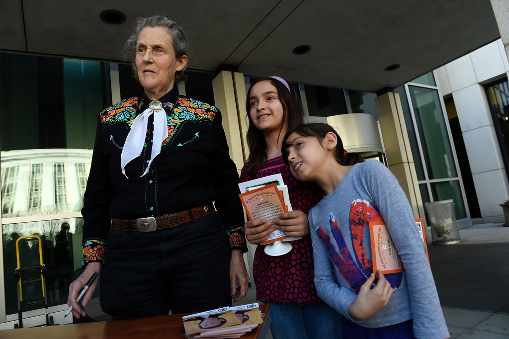 . DENVER, CO - MARCH 3: Dr. Temple Grandin poses for a photo with Karen Llamas, 11, middle and her sister Anna, 8, right, after signing her inventor\'s trading card    outside of the US Patent and Trademark Office on April 3, 2016 in Denver, Colorado. Grandin, who is a professor of animal science at Colorado State University, is the first woman to be honored by the USPTO on it\'s kid friendly inventor trading cards.  Grandin, who is autistic, is well known for her innovative equipment designs that have greatly improved conditions for animals in the livestock industry. (Photo by Helen H. Richardson/The Denver Post)