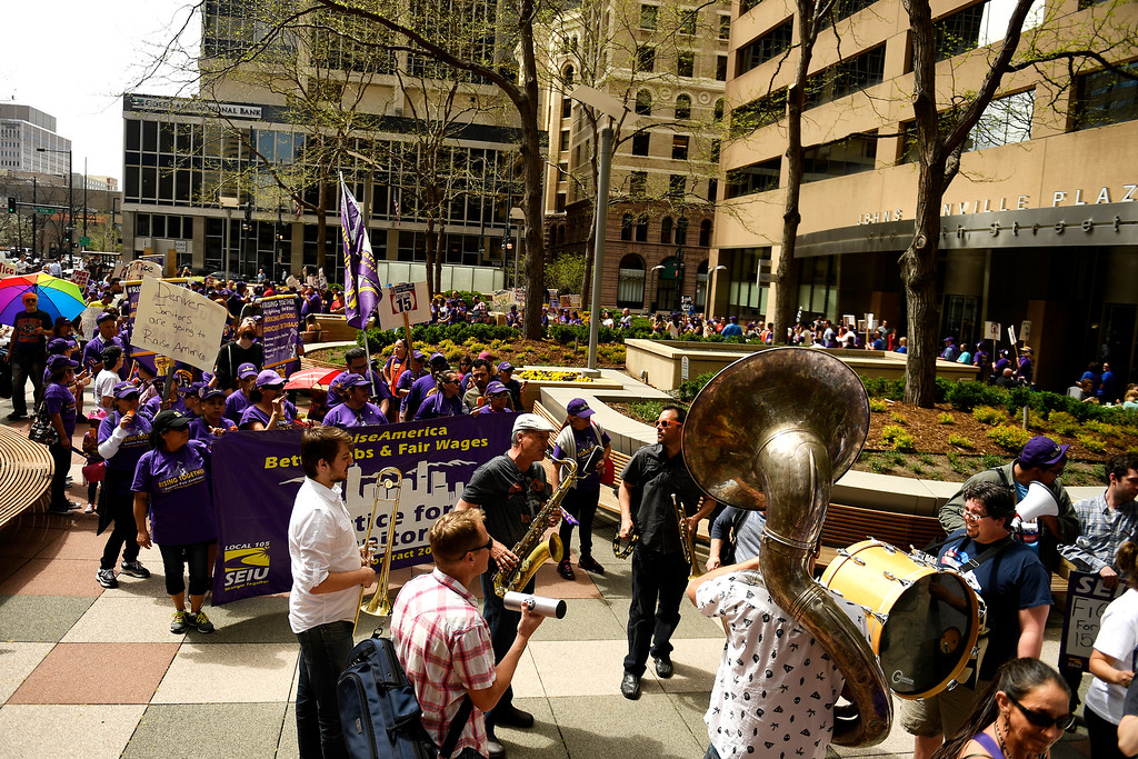 . Denver, CO - ARRIL 14: Denver�s low wage janitors march Johns Manville Plaza. The janitors were joined by local care workers, Fast food, delivery persons and service workers during their  Underpaid Fight for $15 march. April 14, 2016 in Denver, CO. (Photo By Joe Amon/The Denver Post)