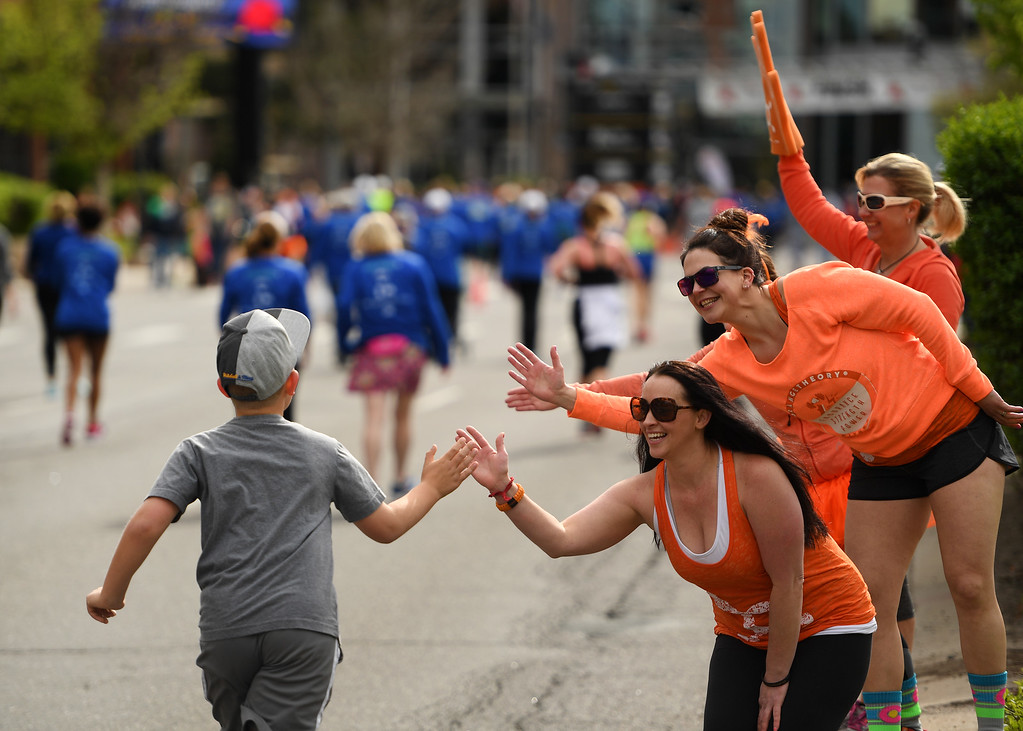 . DENVER, CO - APRIL 24:  Friends Shira Gregory, in front, Julianna Hale, second and Stacie Knapp in the back, high five runners to encourage them toward the finish line during the 34th annual Cherry Creek Sneak road races on April 24, 2016 in Denver, Colorado. The day\'s races included a 10 miler, a 1.5 mile Sneak Sprint, a 5K and a 5 mile run and walk.   (Photo by Helen H. Richardson/The Denver Post)