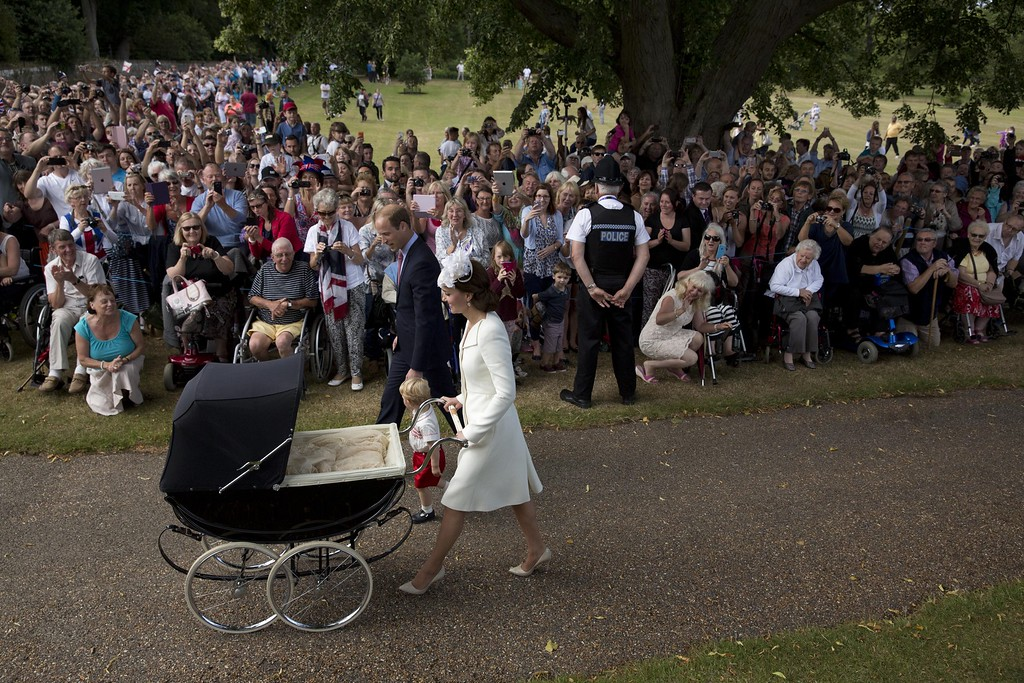 . Crowds look on as Britain\'s Catherine, Duchess of Cambridge, Britain\'s Prince William, Duke of Cambridge and their son Prince George of Cambridge arrive with Princess Charlotte of Cambridge, in her pram for Charlotte\'s Christening at St. Mary Magdalene Church in Sandringham, England, on July 5, 2015. Crowds gathered outside Queen Elizabeth II\'s country residence on Sunday for the christening of Britain\'s baby Princess Charlotte, who it was announced will have five godparents. AFP PHOTO / POOL / MATT DUNHAM