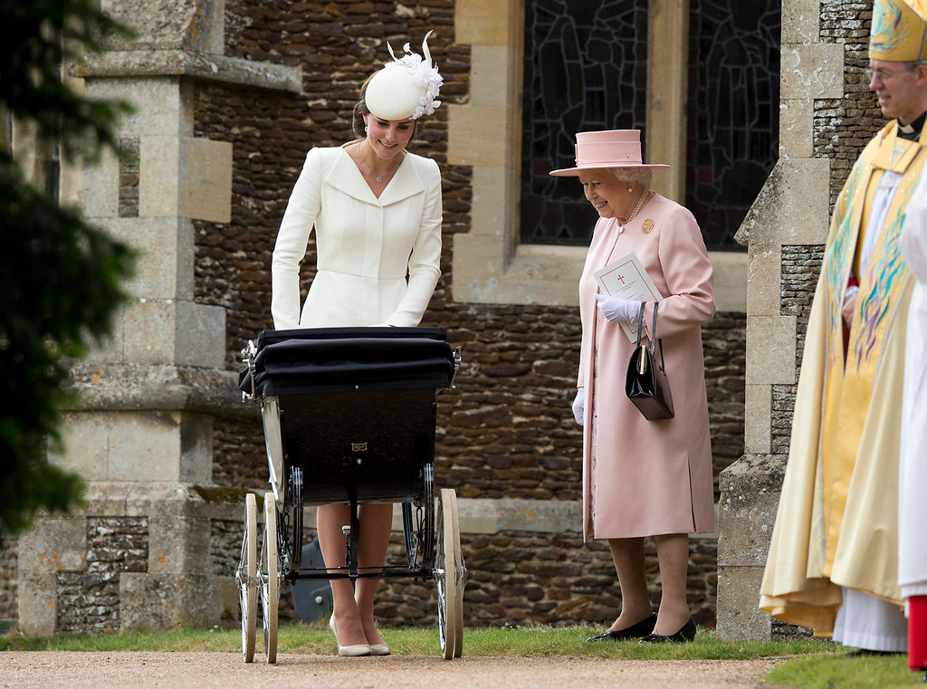 . In this Sunday, July 5, 2015 file photo, Britain\'s Queen Elizabeth II stands with Kate the Duchess of Cambridge whilst pushing Princess Charlotte in a pram as they leave after attending the Christening of Britain\'s Princess Charlotte at St. Mary Magdalene Church in Sandringham, England. Britain\'s Queen Elizabeth celebrates her 90th birthday on Thursday, April 21, 2016. (AP Photo/Matt Dunham, file)