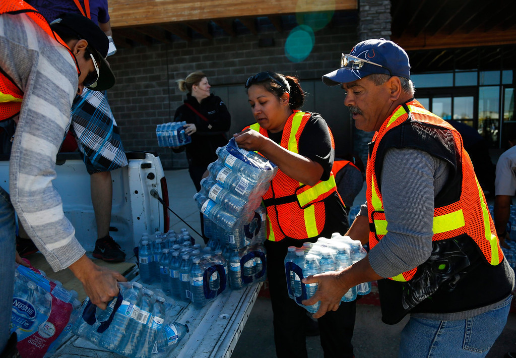 . Volunteers load water for evacuees from the Fort McMurray wildfires at the evacuation center in Lac la Biche, Alberta, Friday, May 6, 2016. More than 80,000 people have left Fort McMurray, in the heart of Canada\'s oil sands, as a wildfire that has devastated the area exploded in size. (Jeff McIntosh/The Canadian Press via AP)