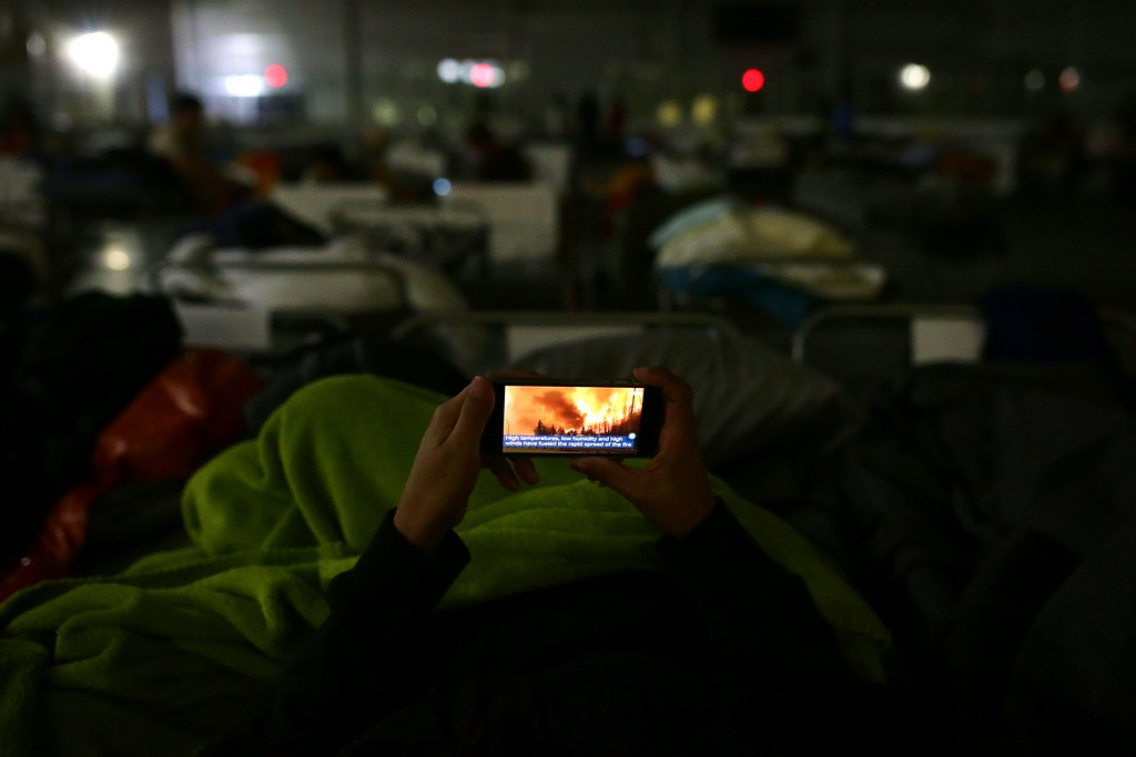 . A displaced person looks at the fire on their mobile phone at a makeshift evacuee center in Lac la Biche, Alberta on May 5, 2016, after fleeing forest fires north of Fort McMurray. Raging wildfires pressed in on the Canadian oil city of Fort McMurray Thursday after more than 80,000 people were forced to flee, abandoning fire-gutted neighborhoods in a chaotic evacuation. No casualties have been reported from the monster blaze, which swept across Alberta\'s oil sands region driven by strong winds and hot, dry weather.  / AFP PHOTO / Cole Burston/AFP/Getty Images