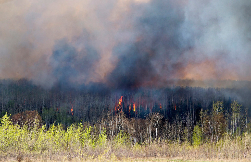 . A wildfire rages through Fort McMurray, Alberta, Wednesday, May 4, 2016. The raging wildfire emptied Canada\'s main oil sands city, destroying entire neighborhoods of Fort McMurray, where officials warned Wednesday that all efforts to suppress the fire have failed.  (Jason Franson /The Canadian Press via AP)