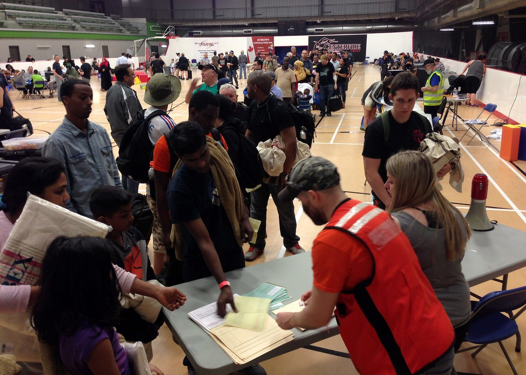 . Evacuees from Fort McMurray  line up to register at an evacuee reception center set up and operated by the regional municipality of Wood Buffalo in Anzac, Alberta, Canada on Wednesday, May 4, 2016.  More than 80,000 residents were ordered to flee the Canadian oil sands city of Fort McMurray, as a wildfire moved into the city, destroying whole neighborhoods. (Mike Allen/The Canadian Press via AP)