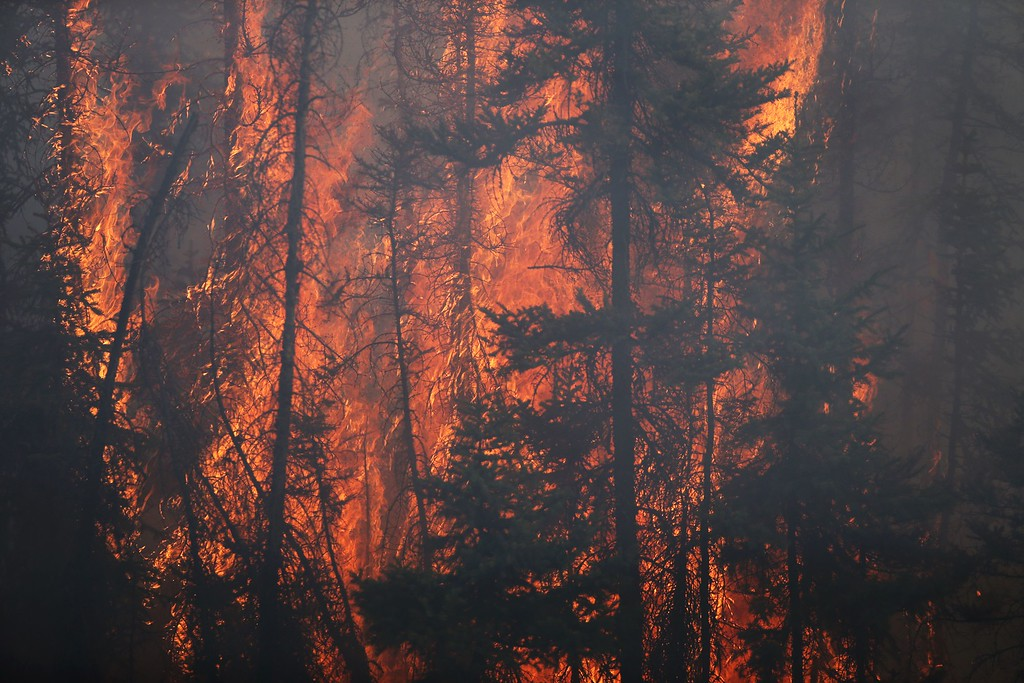 . Flames engulf trees along a highway near Fort McMurray, Alberta, on May 6, 2016.  Canadian police led convoys of cars through the burning ghost town of Fort McMurray Friday in a risky operation to get people to safety far to the south.In the latest chapter of the drama triggered by monster fires in Alberta\'s oil sands region, the convoys of 50 cars at a time are driving through the city at about 50-60 kilometers per hour (30-40 miles per hour) TV footage showed.  / AFP PHOTO / Cole BurstonAFP/Getty Images