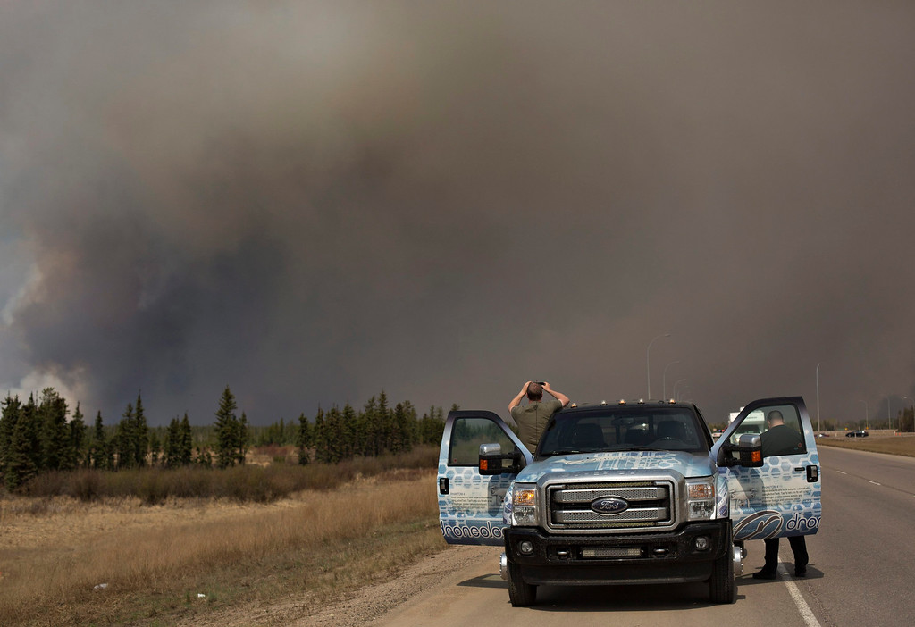 . People stop to take photos of a wildfire south of Fort McMurray, Alberta, Canada on Thursday May 5, 2016. Raging wildfires in the Canadian province of Alberta have moved south, forcing three more communities to evacuate and an emergency operations center to move again. (Jason Franson/The Canadian Press via AP)
