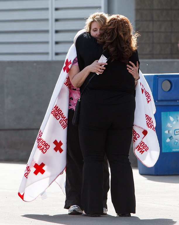 . Evacuees from the wildfires in and around Fort McMurray hug at the evacuation at the Edmonton Expo Centre in Edmonton Alta, on Wednesday, May 4, 2016. A wildfire forced the evacuation of the Canadian oil sands city of Fort McMurray, Alberta, destroying 80 percent of the homes in one neighborhood and extensively damaging property in a number of others, officials said Wednesday. (Codie Mclachlan/The Canadian Press via AP)