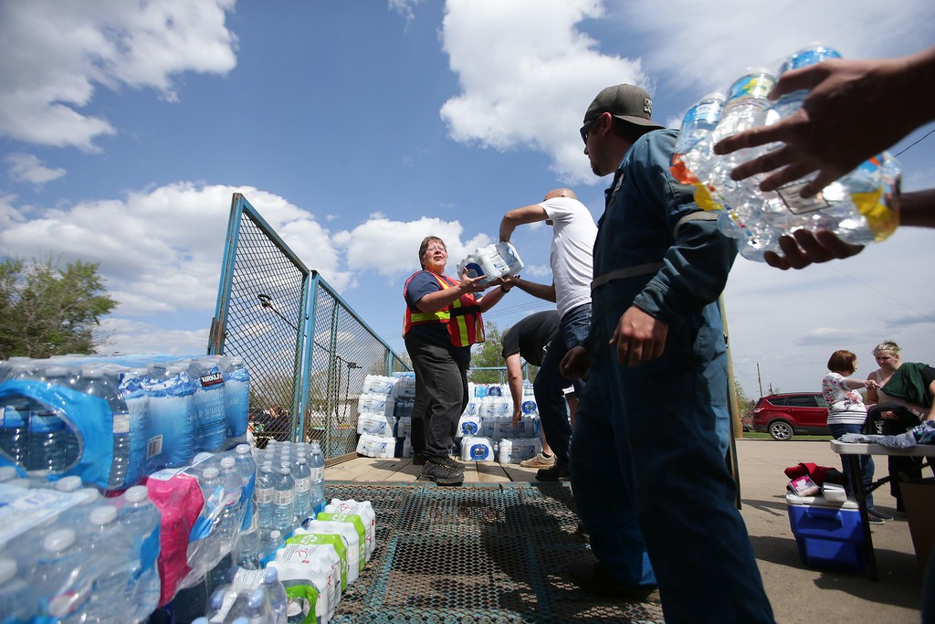 . Volunteers load donated flats of water to be taken to a camp just outside of Wandering River, Canada, on May 5, 2016.  The camp is currently housing more than 400 people displaced by the Fort McMurray forest fires, as many make their way south to Edmonton.  / AFP PHOTO / Cole Burston/AFP/Getty Images