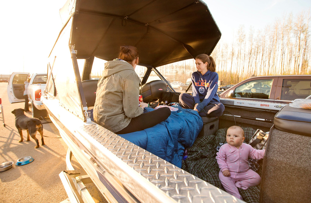 . A family takes refuge in the back of their boat after evacuation at a rest stop near Fort McMurray, Alberta, Canada, on Wednesday, May 4, 2016. Thousands of residents were ordered to flee as flames moved into the Canadian oil sands city, destroying whole neighborhoods. (Jason Franson/The Canadian Press via AP)