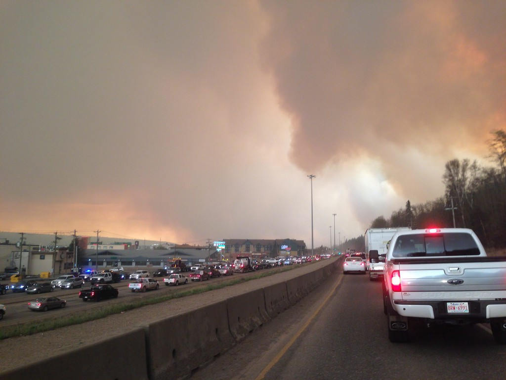 . Smoke from a wildfire rises in the air as cars line up on a road in Fort McMurray, Alberta, Tuesday, May 3, 2016. At least half of a northern Alberta city was ordered evacuated Tuesday as a wildfire whipped by winds engulfed homes and sent ash raining down on residents. (Greg Halinda/The Canadian Press via AP)