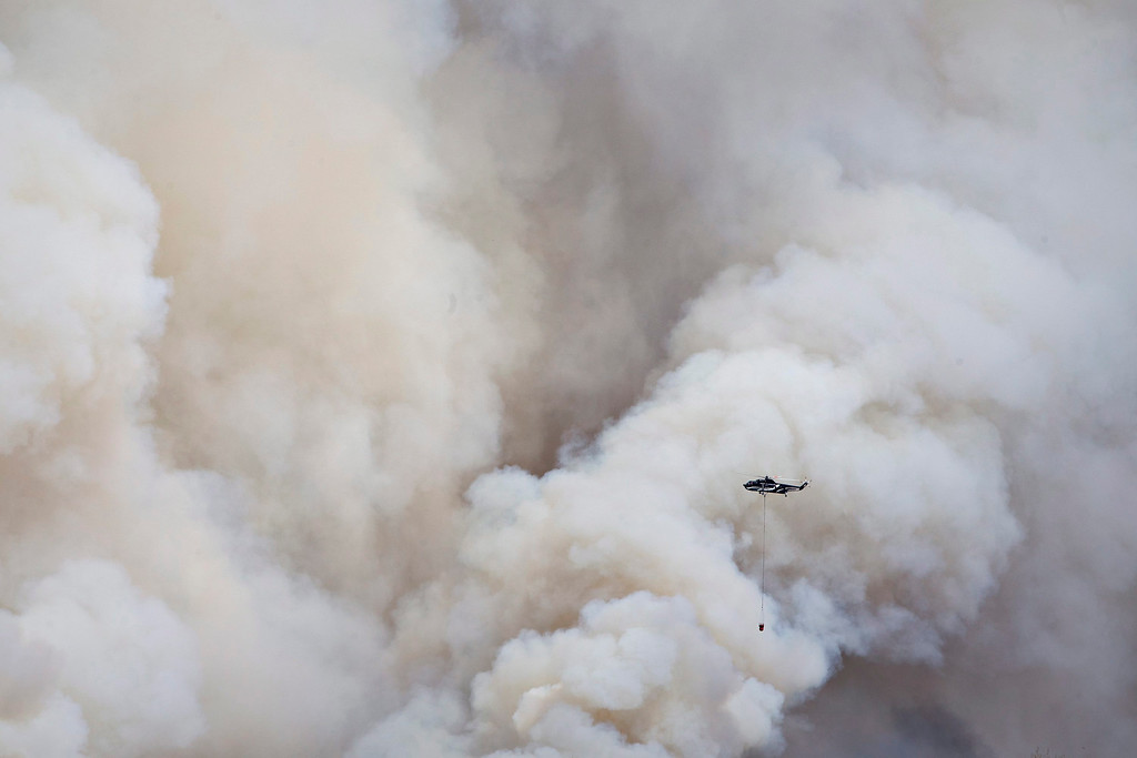 . A helicopter battles a wildfire in Fort McMurray Alberta, on Wednesday, May 4, 2016. The raging wildfire emptied Canada\'s main oil sands city, destroying entire neighborhoods of Fort McMurray, where officials warned Wednesday that all efforts to suppress the fire have failed.  (Jason Franson /The Canadian Press via AP)
