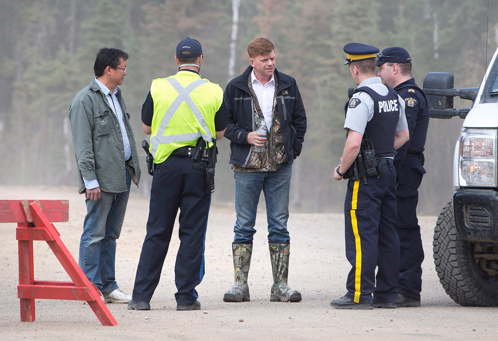 . Alberta Wildrose Leader Brian Jean, center, talks with police near a wildfire in Fort McMurray, Canada, on Thursday, May 5, 2016. Raging wildfires in the Canadian province of Alberta have moved south, forcing three more communities to evacuate and an emergency operations center to move again , taking it far from the devastated oil sands city of Fort McMurray.  Jean\'s house was burned down in the fire.  (Jason Franson/The Canadian Press via AP)