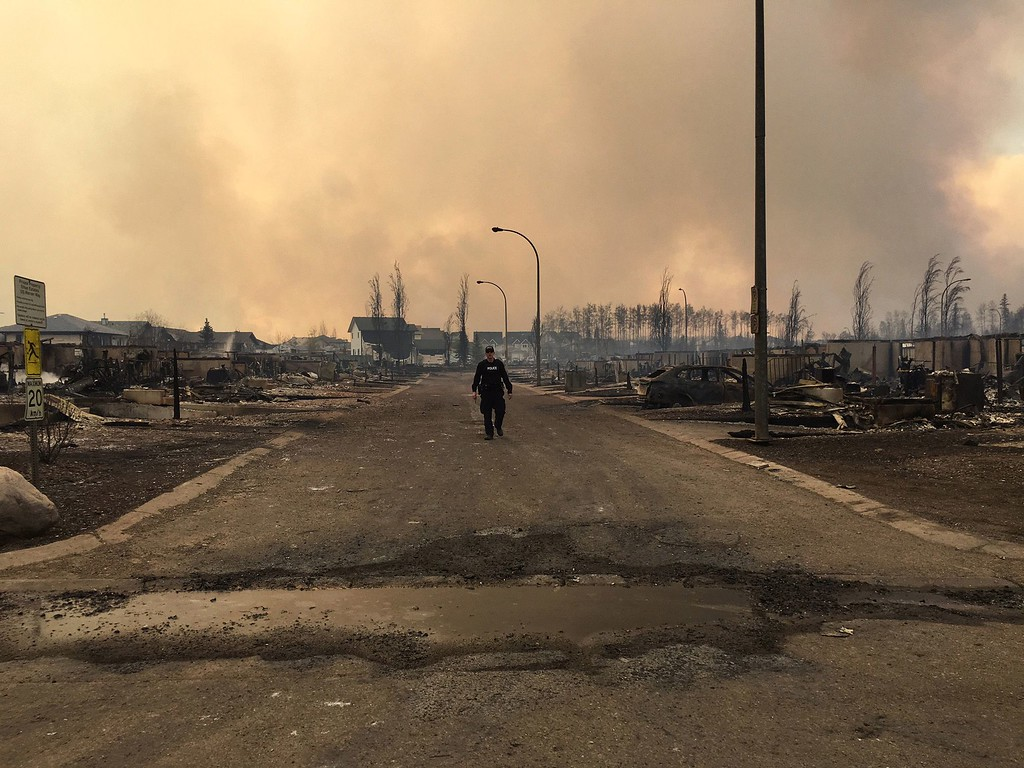 . In this image released by the Alberta RCMP on May 5, 2016, a police officer walks on a road past burned down houses in Fort McMurray, Alberta.   Canada prepared to airlift to safety up to 25,000 people who were forced from their homes by raging forest fires in Alberta\'s oil sands region, and now risk getting trapped north of Fort McMurray. /AFP PHOTO / ALBERTA RCMP/ HO