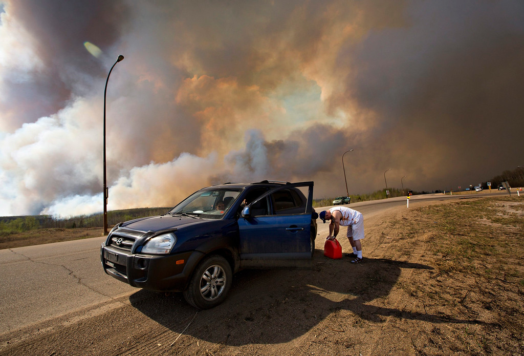 . An evacuee puts gas in his car on his way out of Fort McMurray, Alberta, as a wildfire burns in the background Wednesday, May 4, 2016. The raging wildfire emptied Canada\'s main oil sands city, destroying entire neighborhoods of Fort McMurray, where officials warned Wednesday that all efforts to suppress the fire have failed.  (Jason Franson /The Canadian Press via AP)