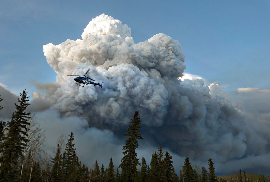 . A helicopter flies past a wildfire in Fort McMurray, Alberta on Wednesday, May 4, 2016. Alberta declared a state of emergency Wednesday as crews frantically held back wind-whipped wildfires that have already torched homes and other buildings in Canada\'s main oil sands city of Fort McMurray, forcing thousands of residents to flee. (Jason Franson /The Canadian Press via AP)