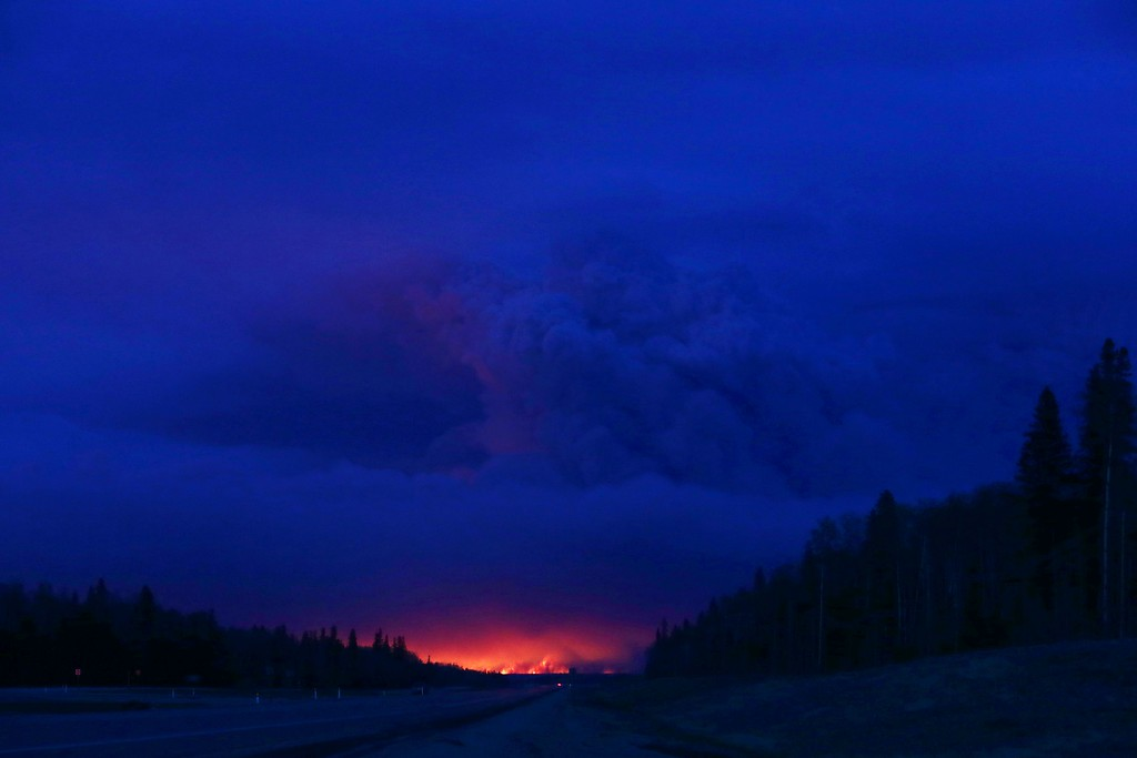 . A plume of smoke hangs in the air as forest fires rage on in the distance in Fort McMurray, Alberta on May 4, 2016. Numerous vehicles can be seen abandoned on the highways leading from the raging forest fires in Fort McMurray and neighboring communities have banded together to offer support in the form of food, water, and gasoline.  / AFP PHOTO / Cole Burston/AFP/Getty Images