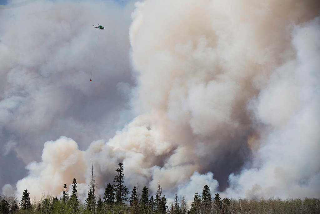 . A helicopter battles a wildfire in Fort McMurray Alberta on Wednesday May 4, 2016. The raging wildfire emptied Canada\'s main oil sands city, destroying entire neighborhoods of Fort McMurray, where officials warned Wednesday that all efforts to suppress the fire have failed.  (Jason Franson /The Canadian Press via AP)