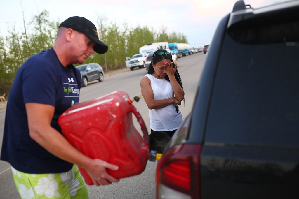 . Marilou Wood fights back tears as husband Jim Wood fills up his car with gas after fleeing forest fires in Fort McMurray on May 4, 2016  Numerous vehicles can be seen abandoned on the highways leading from the raging forest fires in Fort McMurray and neighboring communities have banded together to offer support in the form of food, water, and gasoline.  / AFP PHOTO / Cole Burston/AFP/Getty Images