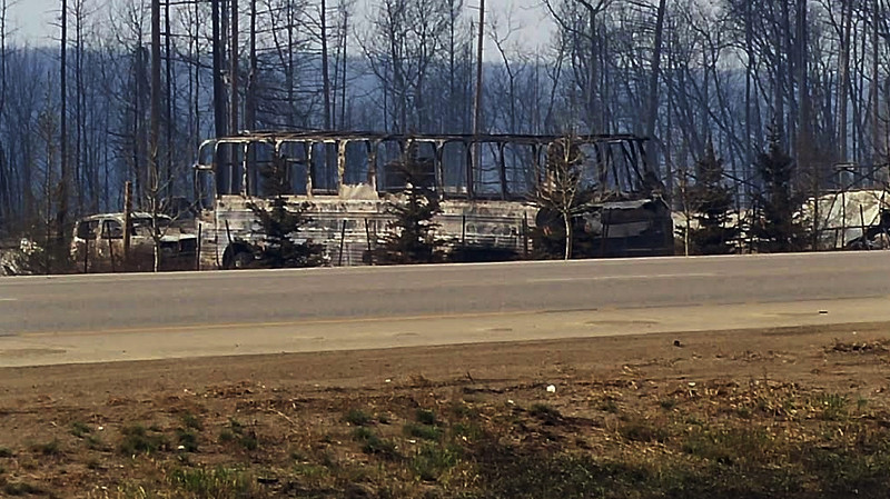 . In this Thursday, May 5, 2016 photo provided by the Royal Canadian Mounted Police Alberta, the charred remains of a bus sit on the side of a road in Fort McMurray, Alberta.  More than 80,000 people have left Fort McMurray, in the heart of Canada\'s oil sands as a wildfire that has devastated the area exploded in size.  (Royal Canadian Mounted Police Alberta via AP)