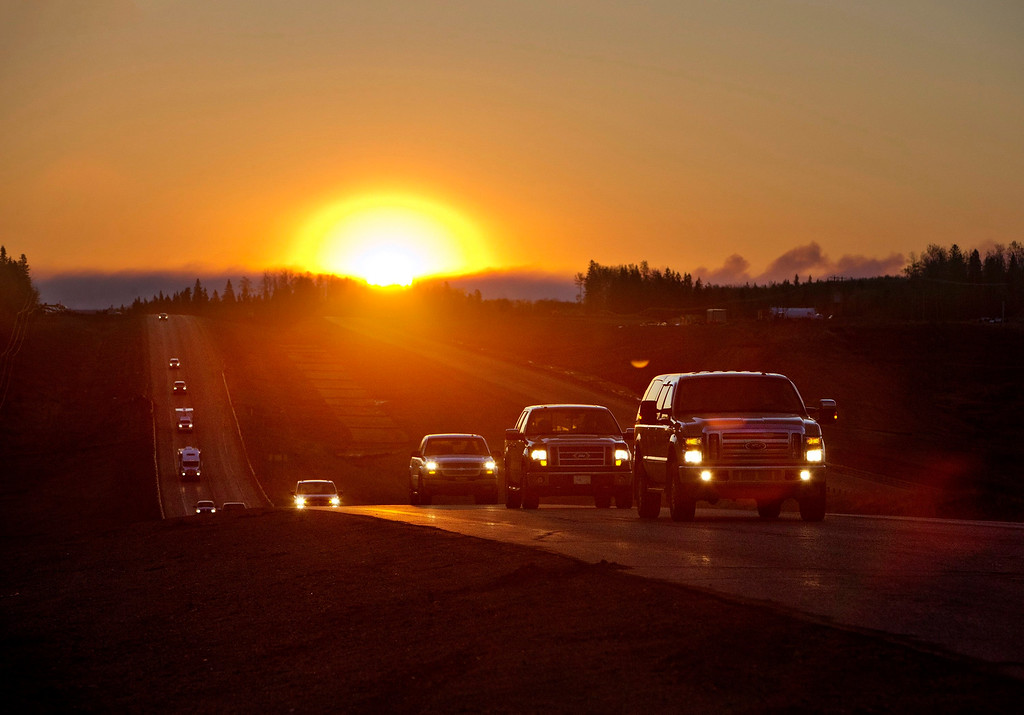 . Evacuees leave Fort McMurray in the early morning, after being stranded north of wildfire in Fort McMurray, Alberta, Canada on Friday, May 6, 2016. The Alberta provincial government, which declared a state of emergency, said more than 1,100 firefighters, 145 helicopters, 138 pieces of heavy equipment and 22 air tankers were fighting the fire, but Chad Morrison, Alberta\'s manager of wildfire prevention, said rain is needed.  (Jason Franson/The Canadian Press via AP)