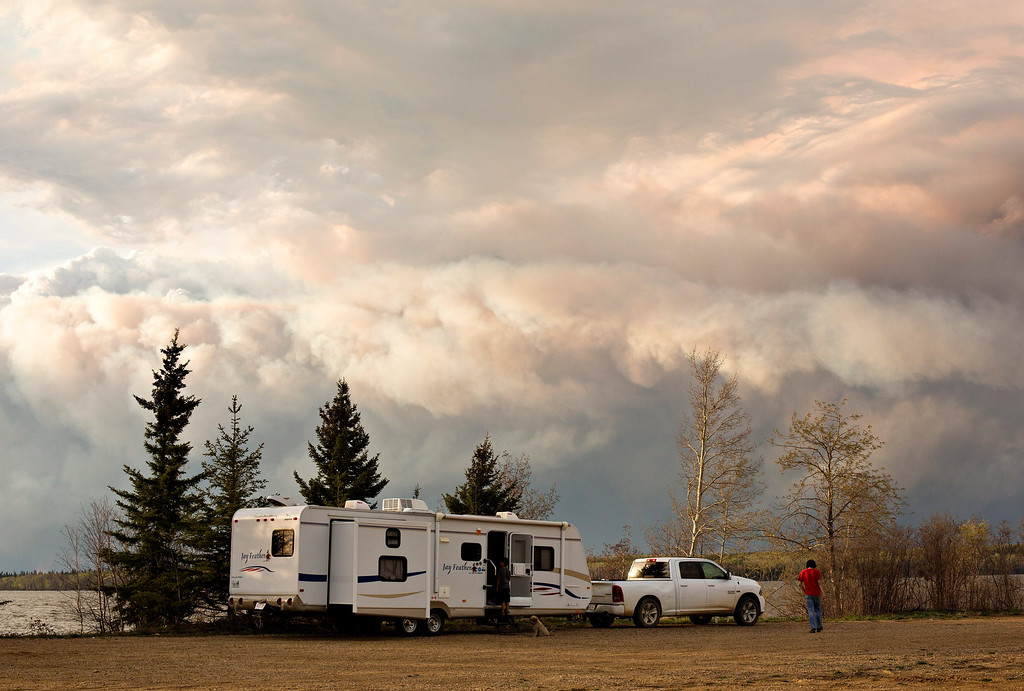 . Evacuees camp by a lake as smoke fills the sky near Fort McMurray, Alberta, on Wednesday, May 4, 2016. Alberta declared a state of emergency Wednesday as crews frantically held back wind-whipped wildfires.  No injuries or fatalities have been reported.  (Jason Franson/The Canadian Press via AP)