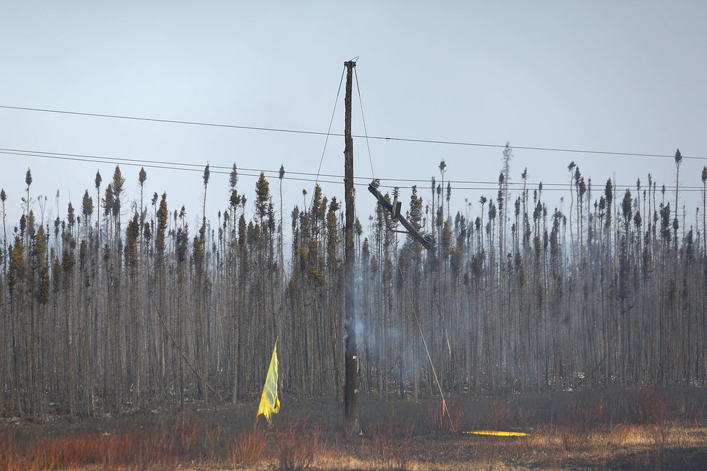 . An electrical pole smolders on the side of  the highway near Fort McMurray, Alberta on May 6, 2016.  Canadian police led convoys of cars through the burning ghost town of Fort McMurray Friday in a risky operation to get people to safety far to the south.In the latest chapter of the drama triggered by monster fires in Alberta\'s oil sands region, the convoys of 50 cars at a time are driving through the city at about 50-60 kilometers per hour (30-40 miles per hour) TV footage showed.  / AFP PHOTO / Cole Burston/AFP/Getty Images