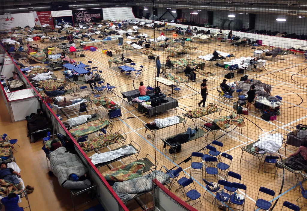 . Cots are set up on the gym floor at an evacuee reception center, operated by the regional municipality of Wood Buffalo in Anzac, Alberta, Canada on Wednesday, May 4, 2016.  More than 80,000 residents were ordered to flee the Canadian oil sands city of Fort McMurray, as a wildfire moved into the city, destroying whole neighborhoods. (Mike Allen/The Canadian Press via AP)
