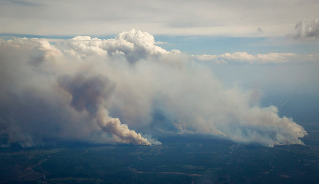 . Wildfires burn in and around Fort McMurray, Alberta, Wednesday, May 4, 2016. The raging wildfire emptied Canada\'s main oil sands city, destroying entire neighborhoods of Fort McMurray, where officials warned Wednesday that all efforts to suppress the fire have failed. (Jeff McIntosh/The Canadian Press via AP)