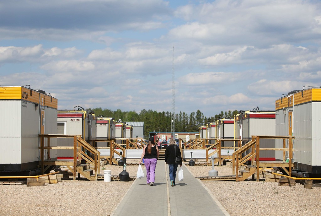 . Two women walk between portable houses at a camp just outside of Wandering River, Canada, on May 5, 2016.  The camp is currently housing more than 400 people displaced by the Fort McMurray forest fires, as many make their way south to Edmonton.  / AFP PHOTO / Cole Burston/AFP/Getty Images
